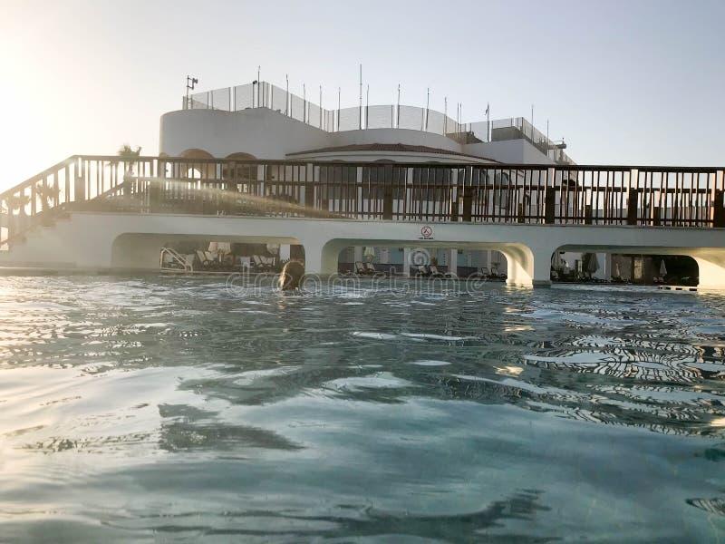En stor stenbyggnad med en fot- bro med bågar ovanför pölen nära vattnet, en pöl mot en blå himmel och en stor sol fotografering för bildbyråer