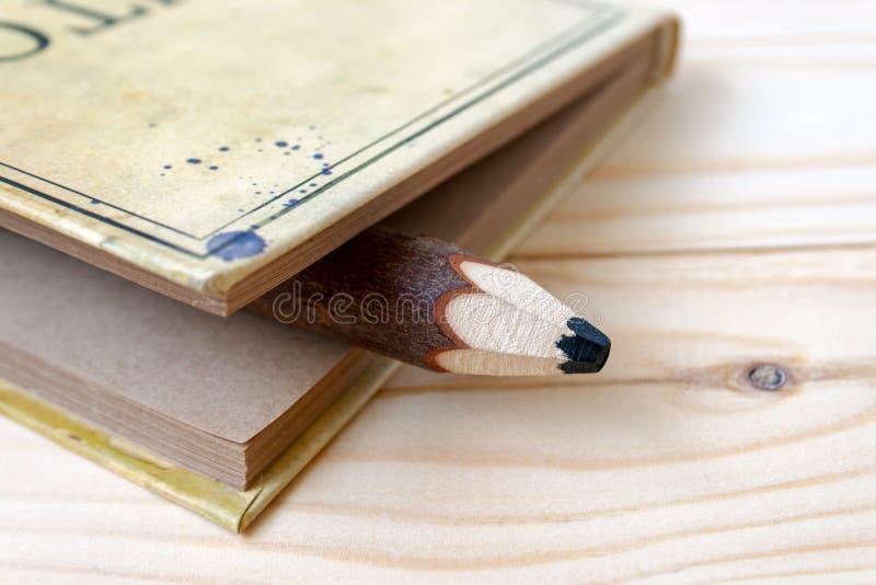 En stor träblyertspenna som klibbar ut ur en notepad med pappers- ark för hantverk som ligger på en träbakgrund fotografering för bildbyråer