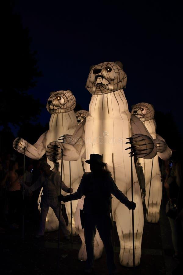 En stor vit artificiell isbjörn på gatan nattetid royaltyfri bild