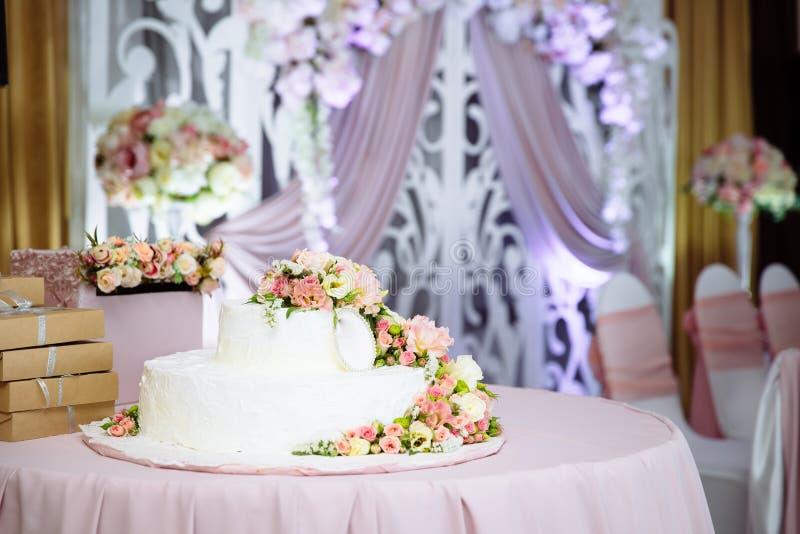 En stor vit bröllopstårta på tabellen som dekoreras med nya blommor Förberedelse för bröllopet, dekorera och idén arkivbild