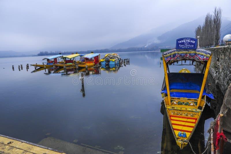 En storartad sikt av Kashmir nära sjön på Srinagar Ett folk som använder här ett colourfullfartyg för att tilldra en besökare royaltyfri foto