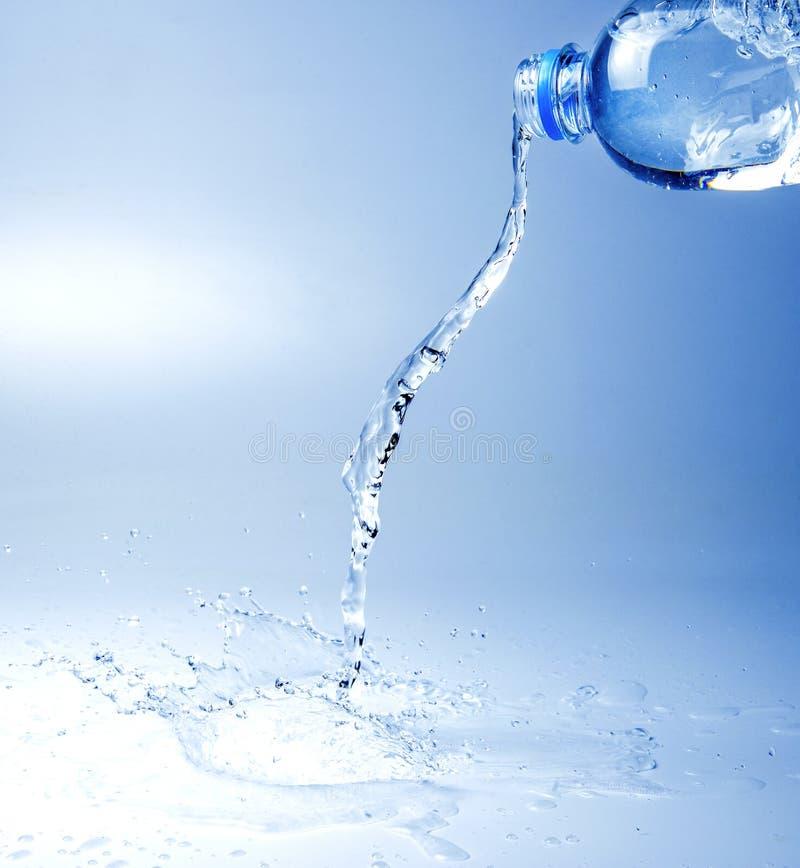 En str?le av kolsyrat vatten som flyr fr?n flaskan Vit bl? signalbild royaltyfri foto
