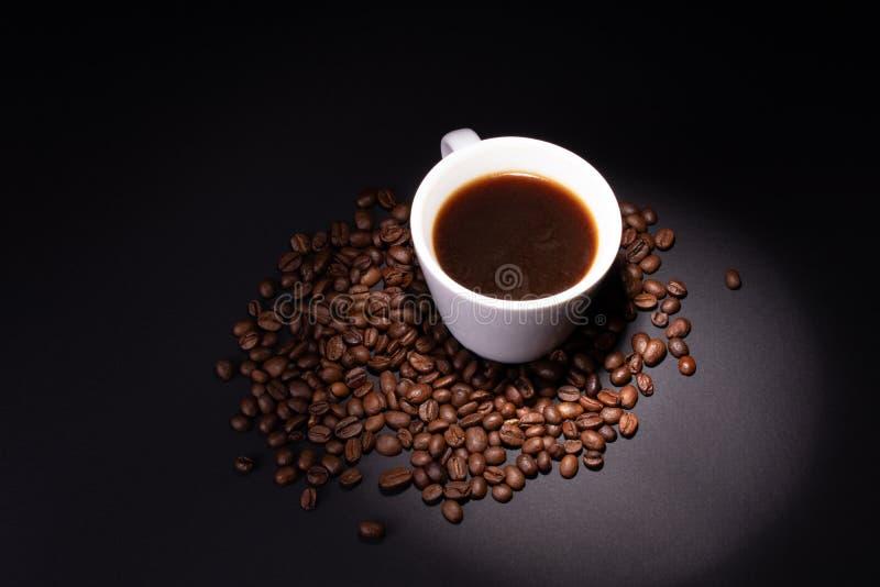 En stråle av ljus riktas på ett kopp kaffeanseende i en hög av kaffebönor royaltyfri foto