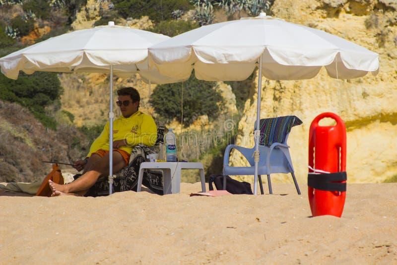 En strandlivvakt under skuggan av hans solbrolly, medan avläsa stranden i Albuferia i Portugal royaltyfria foton