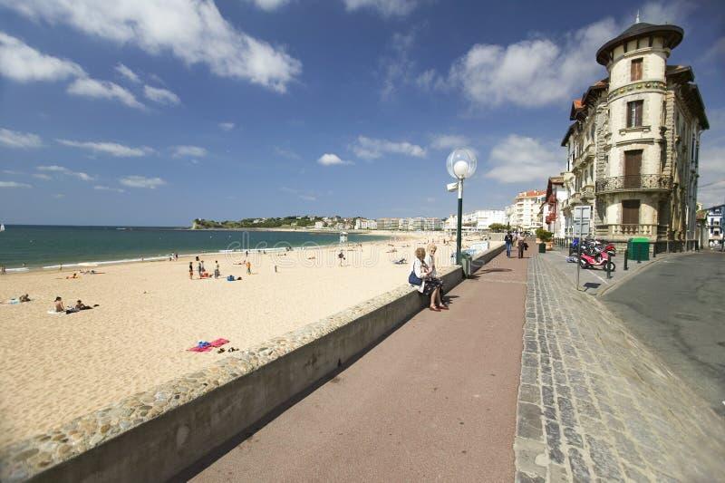 En strandpromenad på stranden av St Jean de Luz, på skjulbasken, södra västra Frankrike, ett typisk fiskeläge i Franska-basken royaltyfria bilder