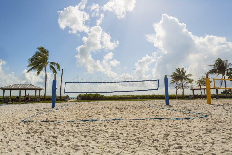 En strandvolleyboll förtjänar på en solig strand, med palmträd arkivbilder