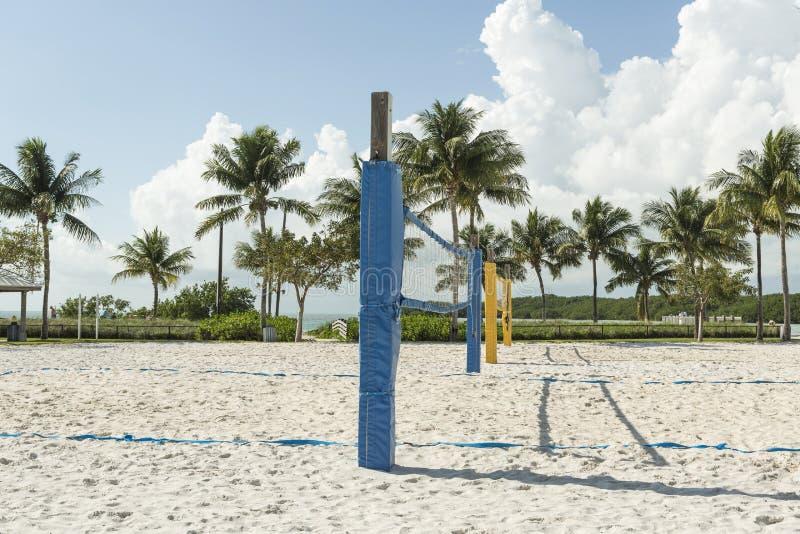 En strandvolleyboll förtjänar på en solig strand, med palmträd arkivfoton