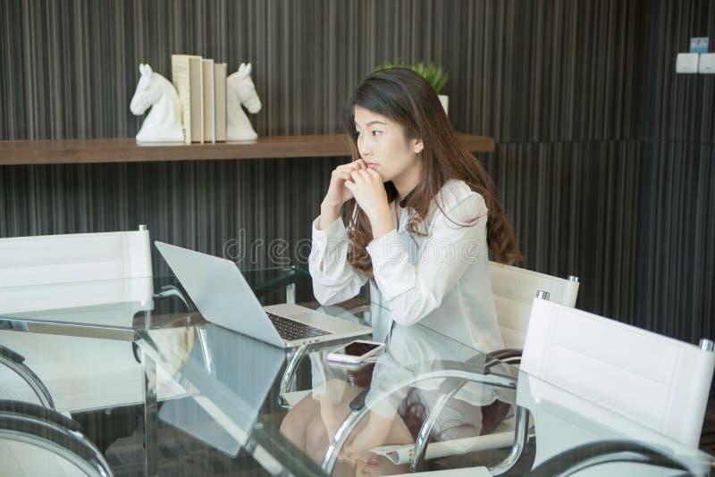 En stressad asiatisk affärskvinna som använder en bärbar dator arkivfoto