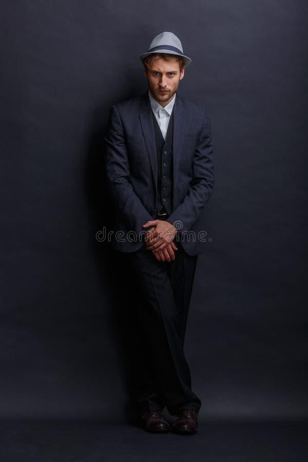 En strikt man i en strikt dräkt och hatt, poserar med hans händer vikta tillsammans arkivfoto