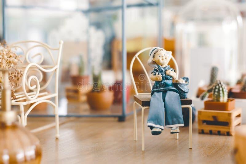 En stuckatur som sitter på liten stol, och de är på trätabellen i coffee shop arkivbild