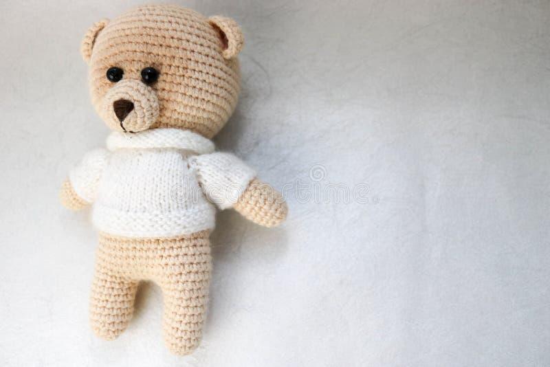 En stucken hemlagad härlig gullig liten björn i en vit tröja med blåtiror, en mjuk leksak som binds med beigea stora trådar på en arkivbild