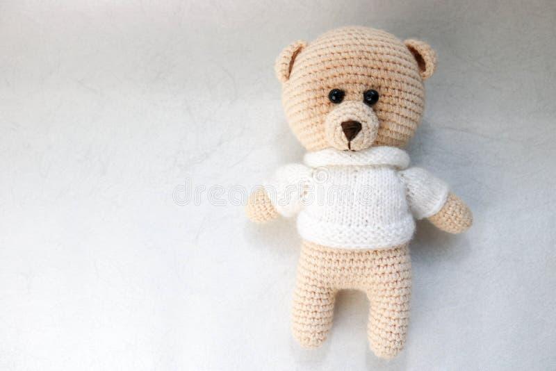 En stucken hemlagad härlig gullig liten björn i en vit tröja med blåtiror, en mjuk leksak som binds med beigea stora trådar på en royaltyfri fotografi