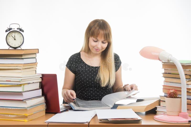 En student på en tabell som skräpas ner med böcker i arkiv med ett leende som vänder sidorna i en mapp royaltyfri bild