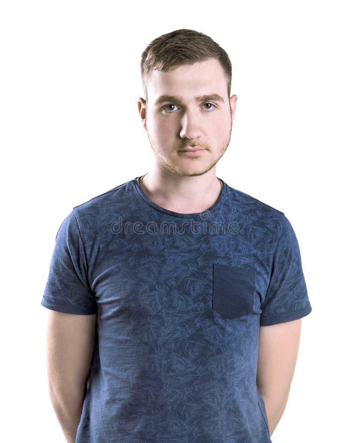 En student som isoleras på en vit bakgrund En ung man som poserar i ett mörker - blå t-skjorta En stark grabb med ett neutralt ut arkivbild