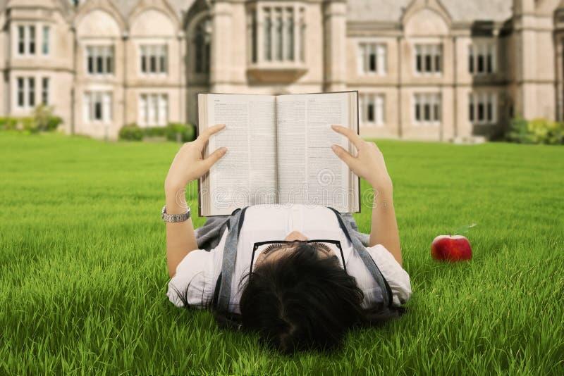 En student som läser en utomhus- bok arkivbild