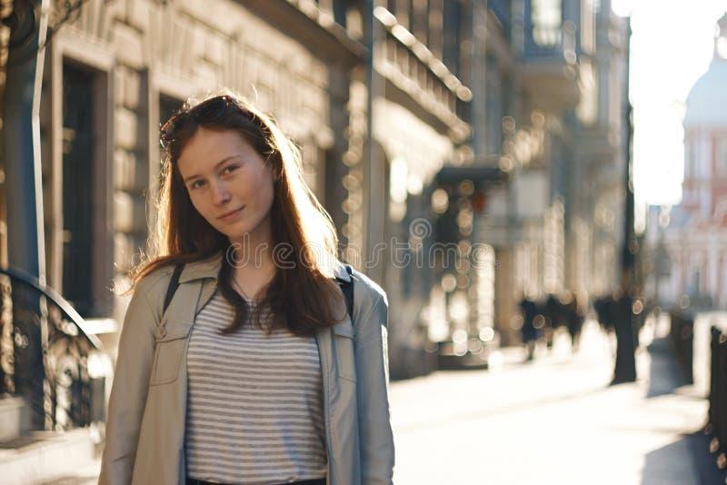 En studentflicka står på bakgrunden av en stadsgata arkivbild