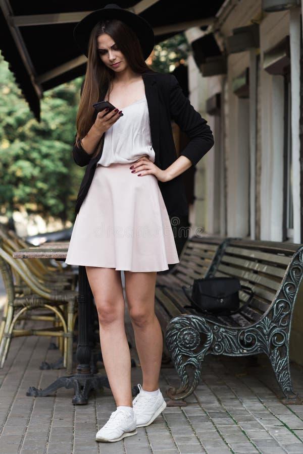En stylishly klädd flicka står nära marmorkaffetabellen och en träbanch och bläddrar newsfeed i facebook hon är weaen royaltyfria bilder