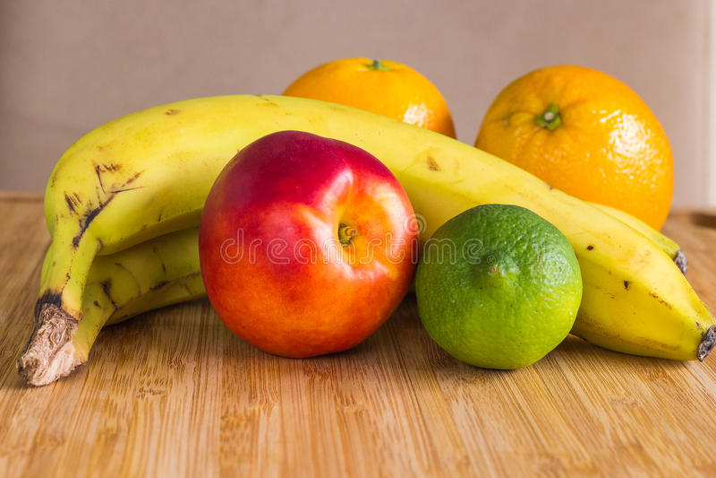 En sund fruktordning med en nektarin, limefrukt, bananer, apelsiner royaltyfria bilder