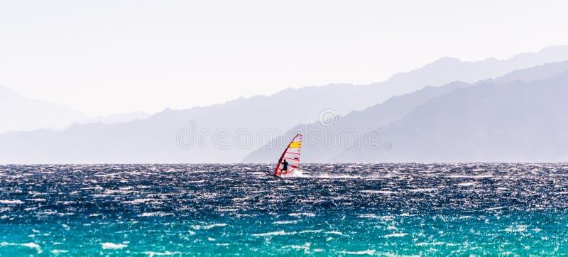 En surfare rider på en bakgrund av höga berg i Egypten Dahab södra Sinai arkivfoto