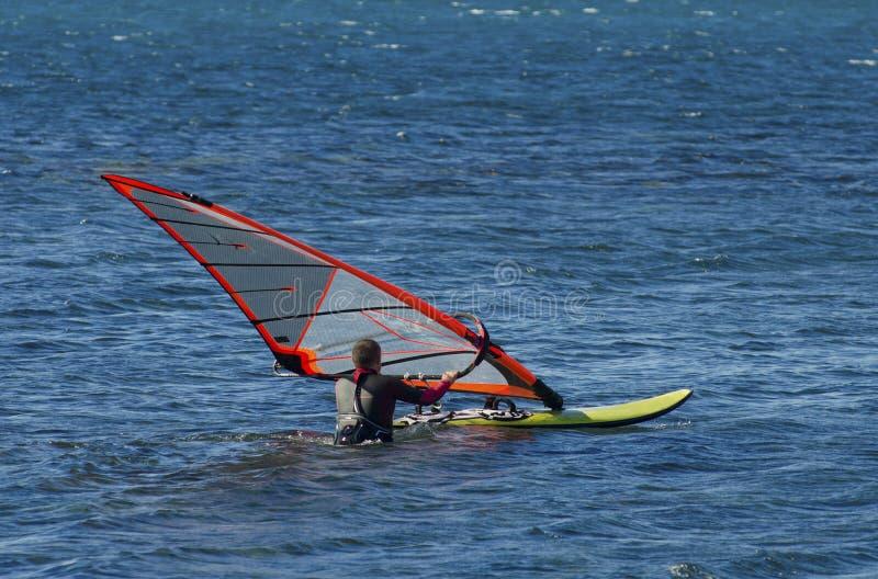 En surfare rider p? havet i stillhet, ljus vind arkivfoto
