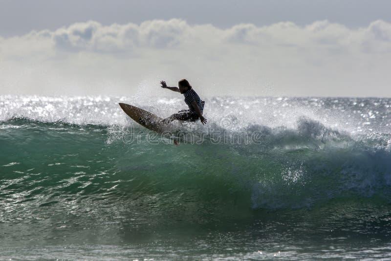 En surfare rider en punktavbrottsvåg på den Arugam fjärden i Sri Lanka royaltyfri foto