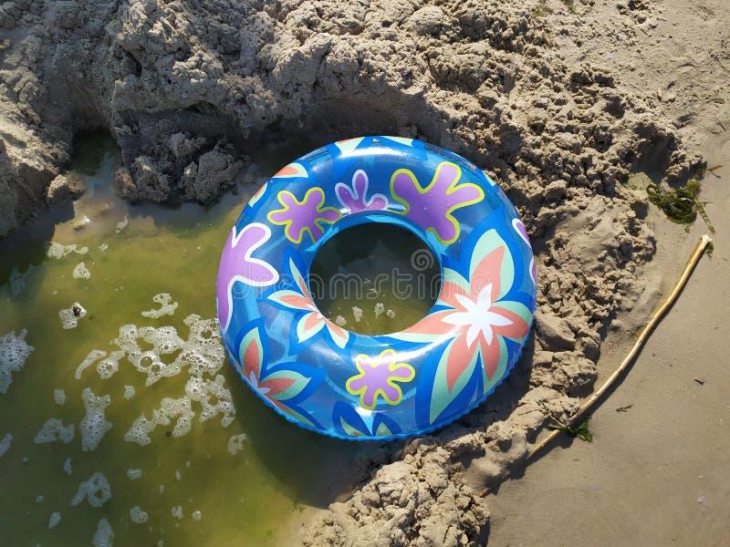 En sväva cirkel för barn ligger på den sandiga flodstranden nära vattnet arkivfoton