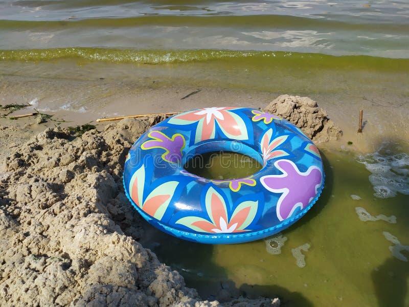 En sväva cirkel för barn ligger på den sandiga flodstranden nära vattnet royaltyfri foto