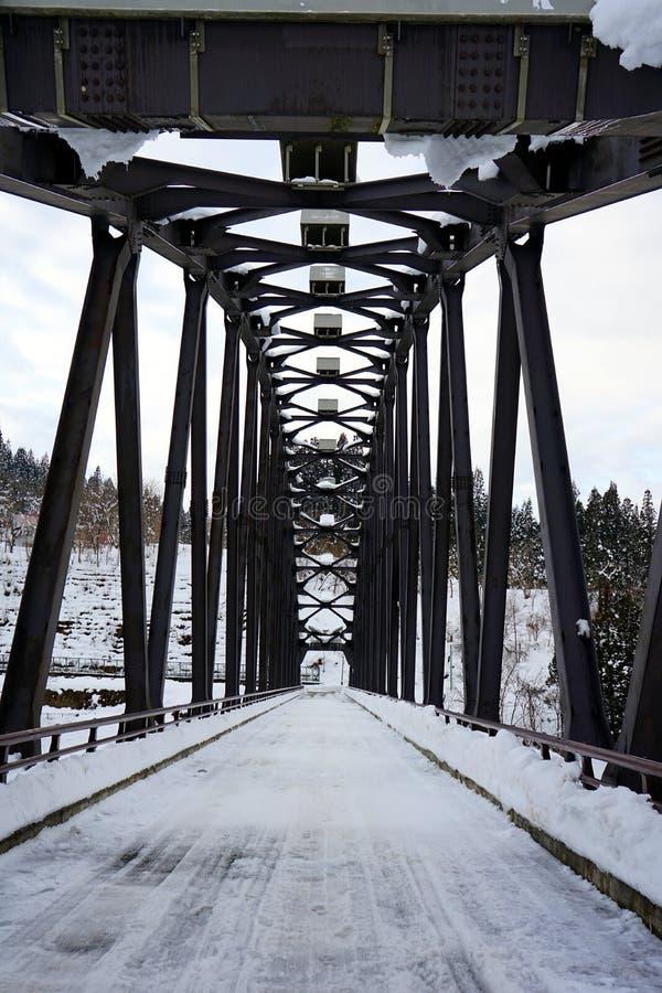 En svart järnbroräkning med snö arkivfoton
