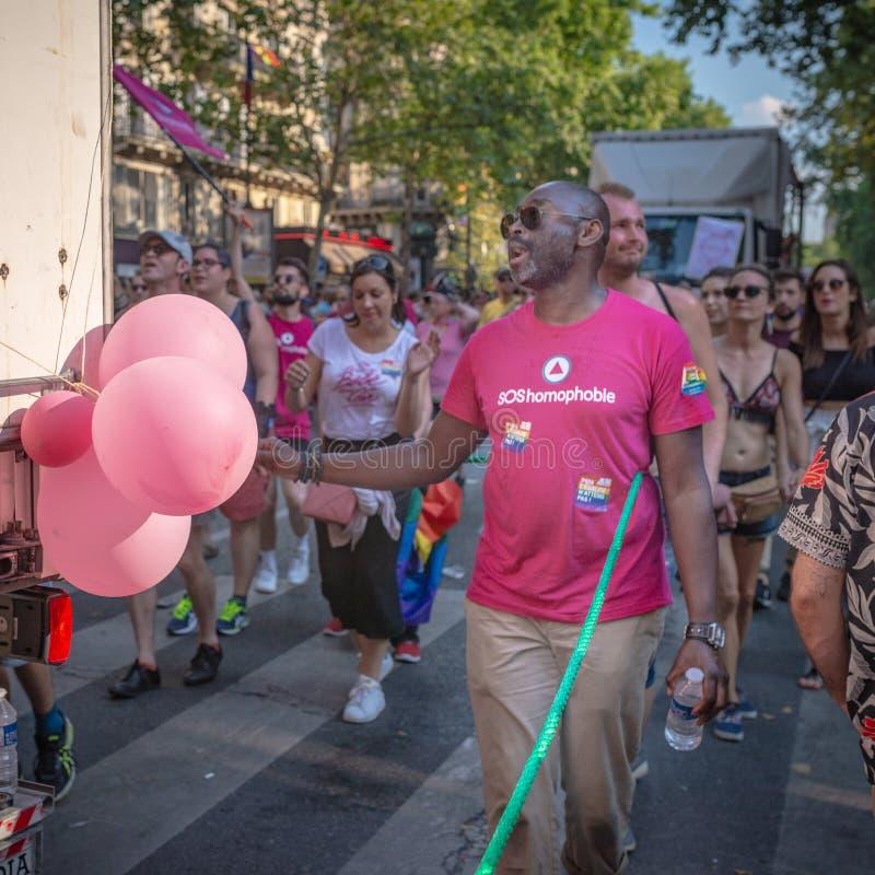 En svart man som bär en rosa t-skjorta på Paris 2018 Gay Pride fotografering för bildbyråer
