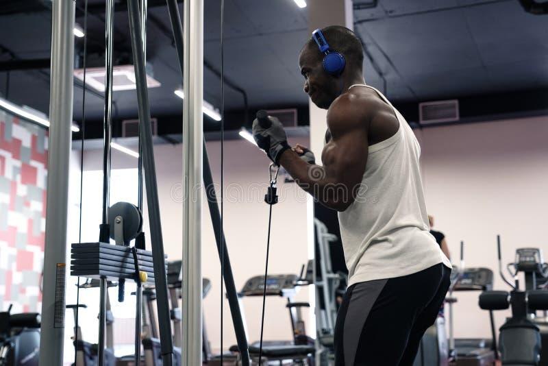 En svart muskulös man i en T-tröja och hörlurar skakar hans händer med en simulator i idrottshallen royaltyfri fotografi