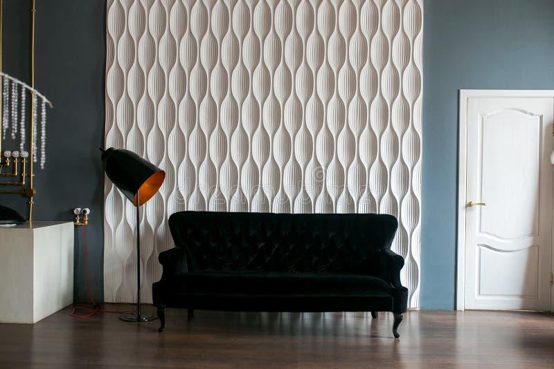 En svart soffa och en svart golvlampa mot en vit präglad vägg i vindutrymmet royaltyfri foto