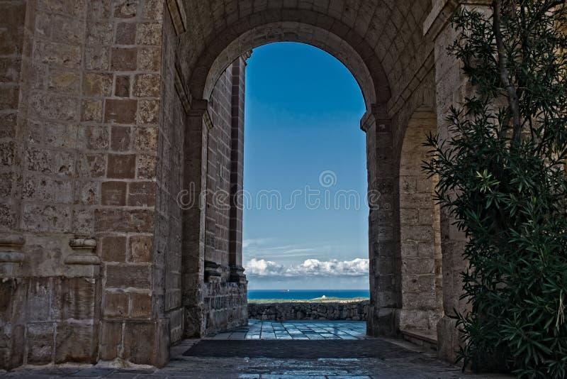 En syn på Mellieha, Malta genom en båge royaltyfria foton