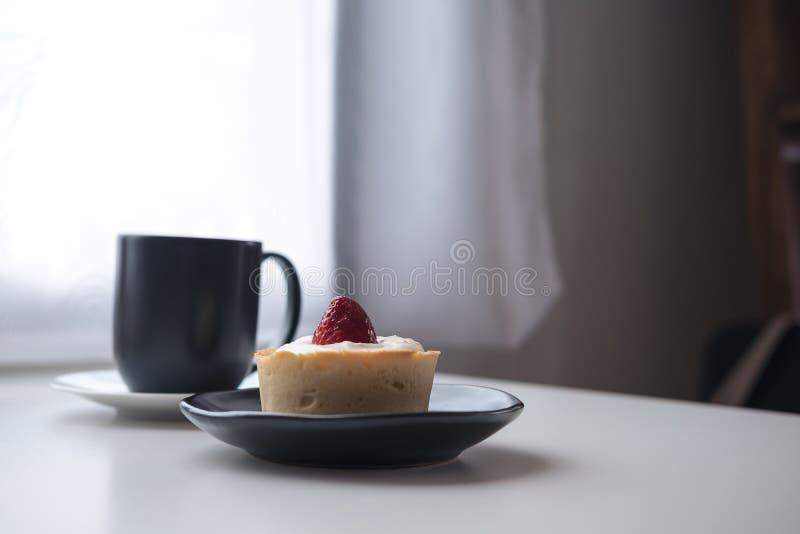 En syrlig jordgubbeost, en svart kopp av varmt kaffe och kaktus på trätabell- och gardinbakgrund för vit tappning royaltyfria foton