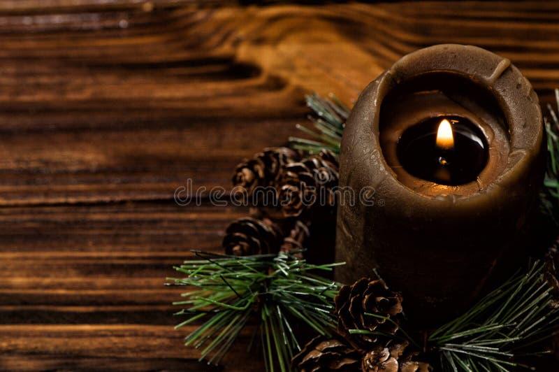 En tänd brun stearinljus dekoreras med en prydlig filial med små kottar Bruna träbräden på bakgrunden royaltyfri foto
