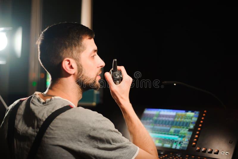 En tändande tekniker arbetar med ljusteknikerkontroll på konsertshowen Yrkesmässig ljus blandare, blandande konsol arkivfoton
