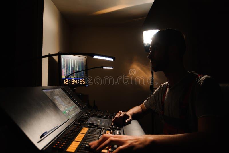 En tändande tekniker arbetar med ljusteknikerkontroll på konsertshowen Yrkesmässig ljus blandare, blandande konsol royaltyfri fotografi