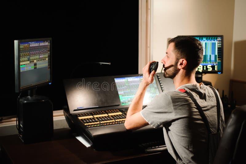 En tändande tekniker arbetar med ljusteknikerkontroll på konsertshowen Yrkesmässig ljus blandare, blandande konsol royaltyfri bild