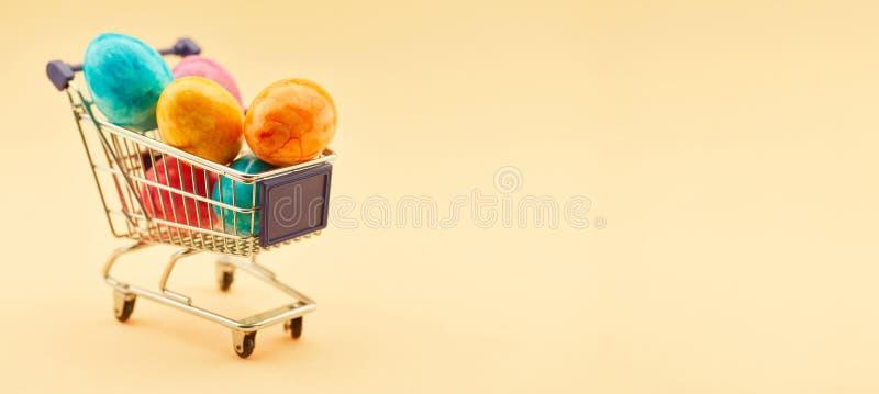 En-tête de Pâques avec le caddie complètement des oeufs de pâques photos stock