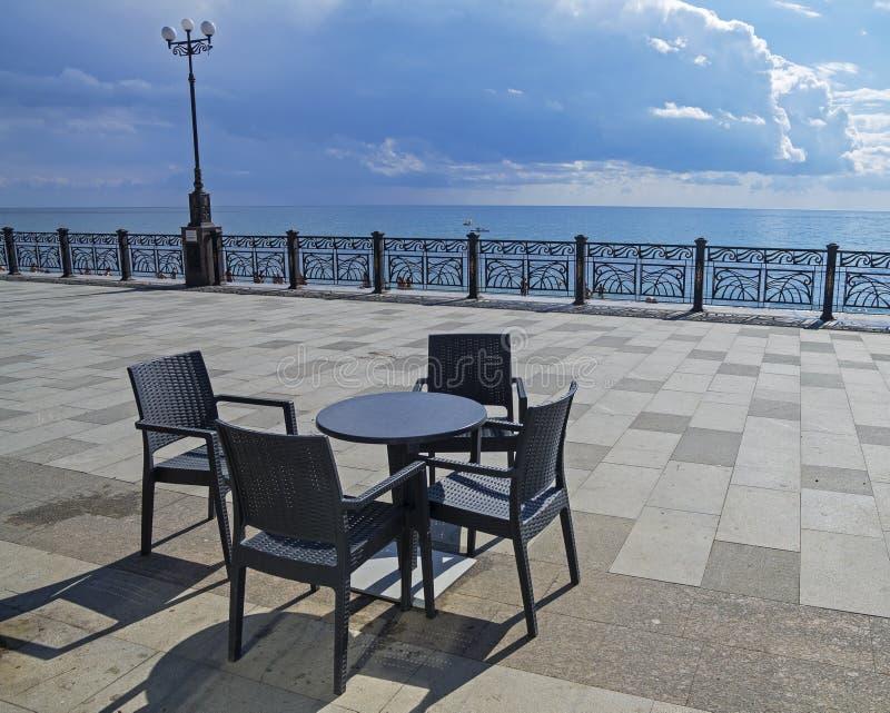 En tabell och fyra stolar på en tom sjösida crimea royaltyfri foto