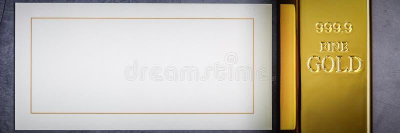 En tacka av guld- metallguldtacka av den rena briljanten på en grå texturerad bakgrund fotografering för bildbyråer