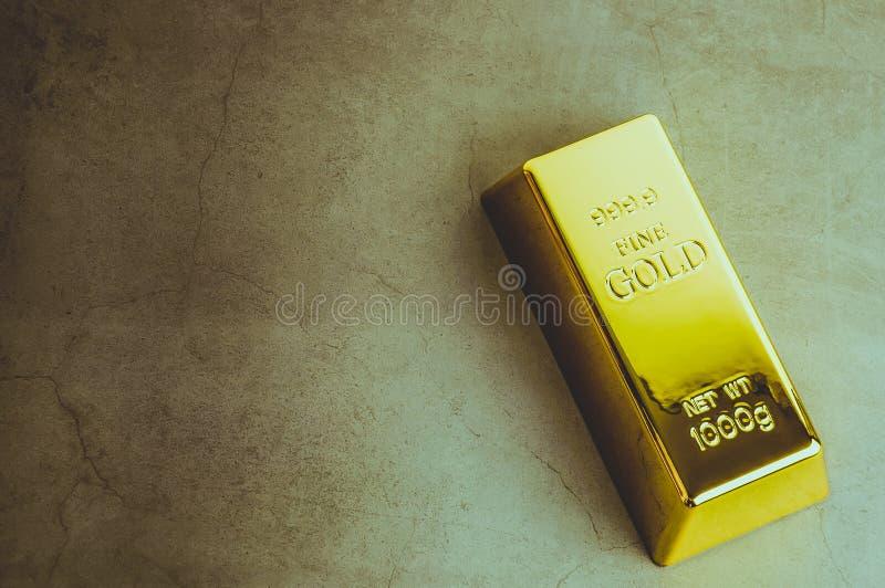 En tacka av guld- metallguldtacka av den rena briljanten som lokaliseras diagonalt på en grå texturerad bakgrund arkivfoton
