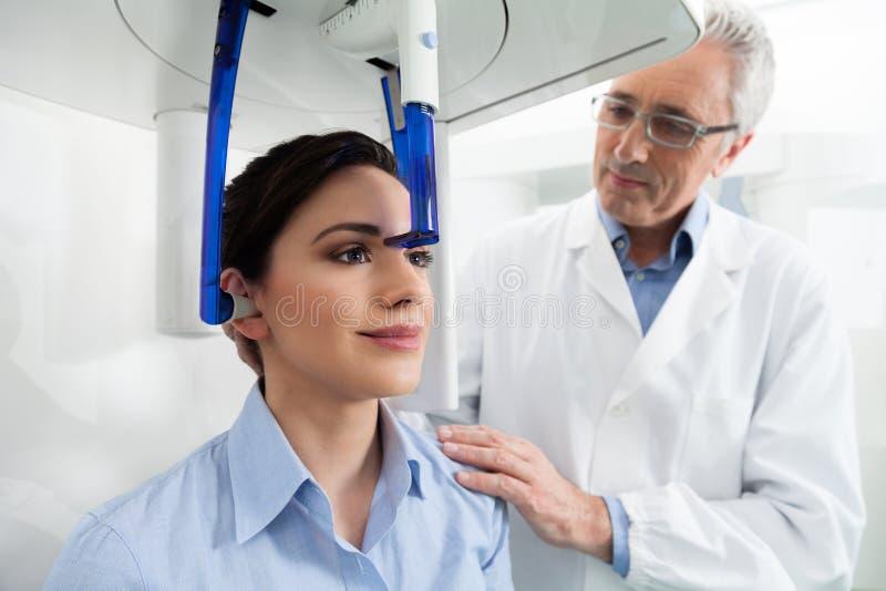En tandläkare som kontrollerar hans kvinnliga patient för en röntgenstrålepanoram arkivfoto
