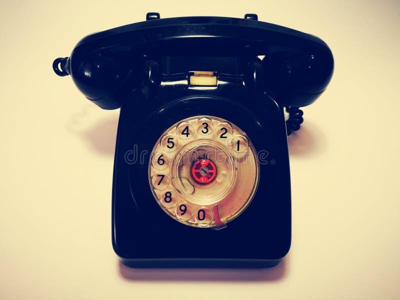 En tappning och en antik telefon med vit bakgrund arkivfoton