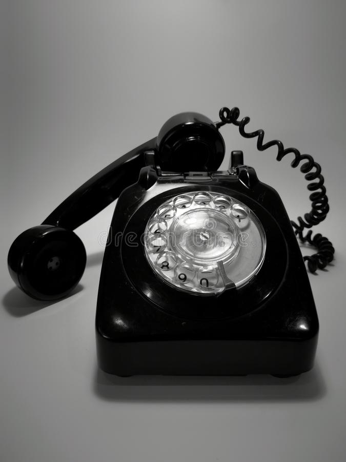 En tappning och en antik telefon med vit bakgrund arkivbilder