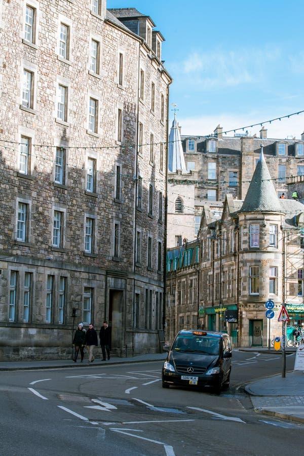 En taxi som korsar den Cowgate gatan i Edinburg Skottland arkivfoton