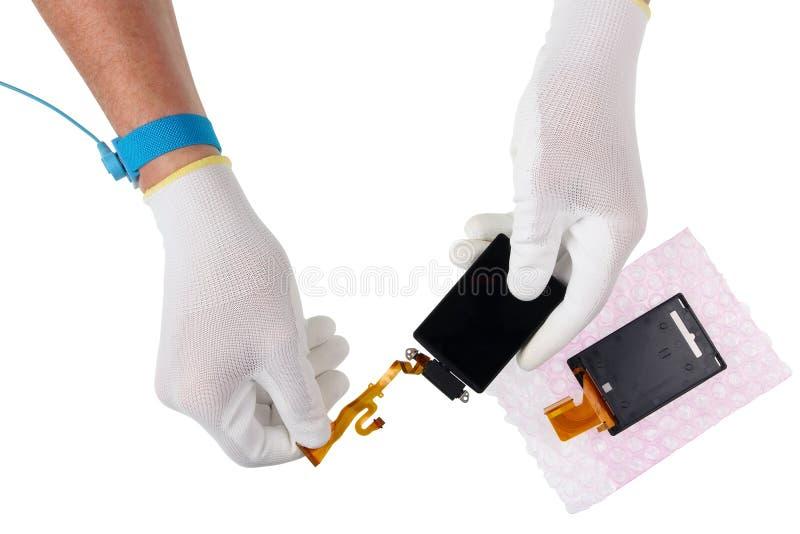 En tekniker i antistatiska handskar för repairman rymmer skärmen t arkivbild
