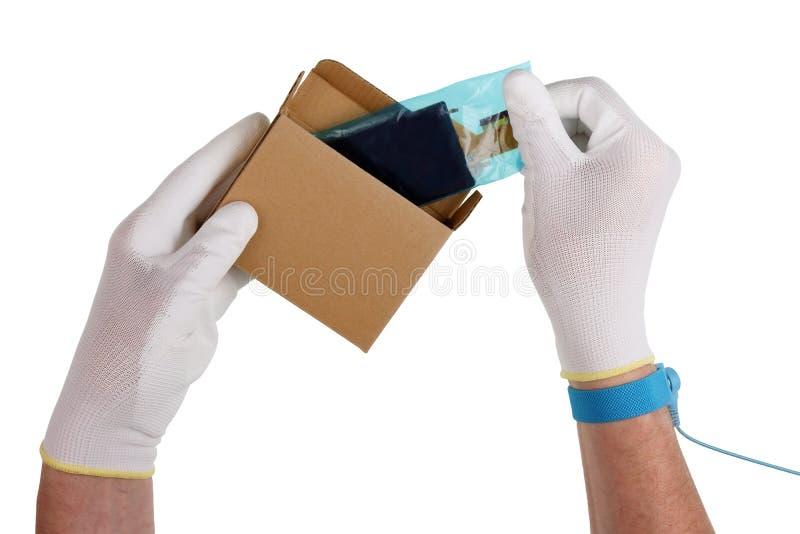 En tekniker i antistatiska handskar packar upp skärmen för att reparera royaltyfri bild