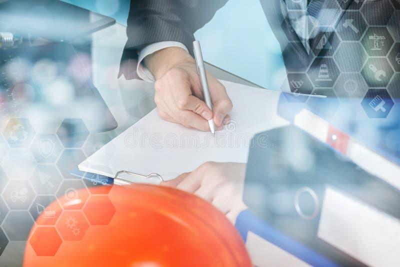 En tekniker undertecknar avtalet i kontoret arkivfoto