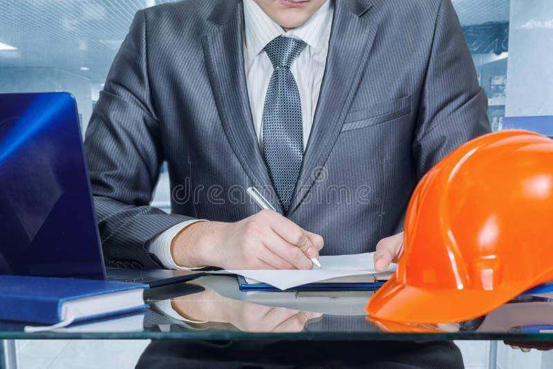 En tekniker undertecknar dokument i kontoret royaltyfri foto