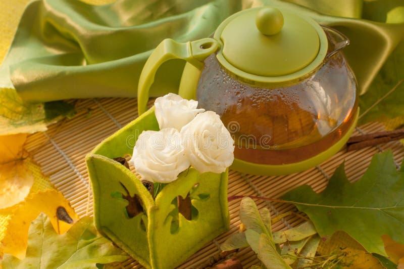 En tekruka, en kopp av örtte, blommor och höstsidor royaltyfri foto